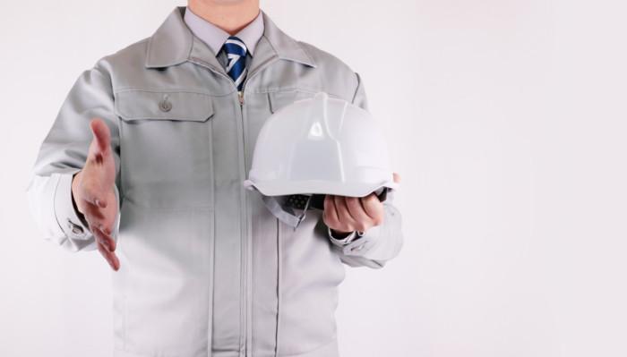 握手を求めるヘルメットを持った作業員
